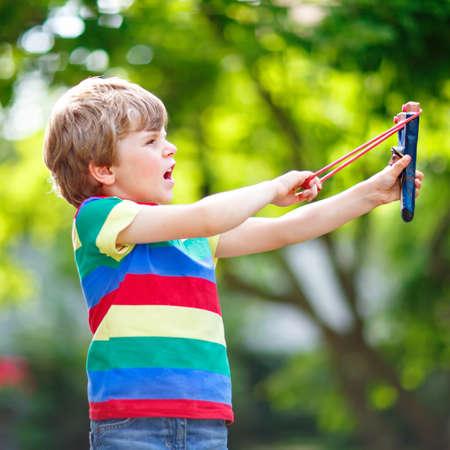 Funny little kid boy shooting wooden slingshot against green tree background. Child having fun in summer