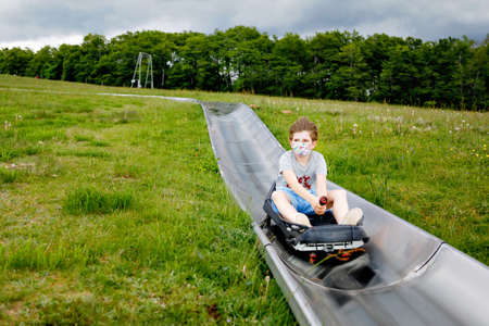Young school kid boy having fun riding summer toboggan run sled down a hill in Hoherodskopf, Germany. Active child with medical mask making funny activity otudoors. Family leisure with kids. Banque d'images