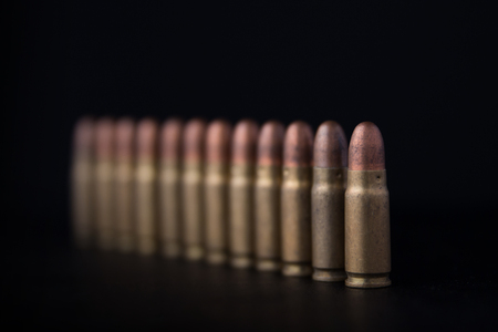 shootings: Pistol bullets stand in a row diagonally. The first bullet in the field. Stock Photo