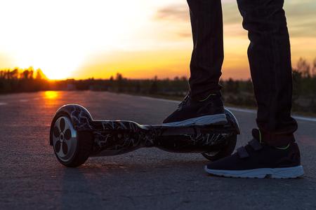 男は、夕日に向かって移動を開始する黒のジャイロの彼の右の足を置きます。