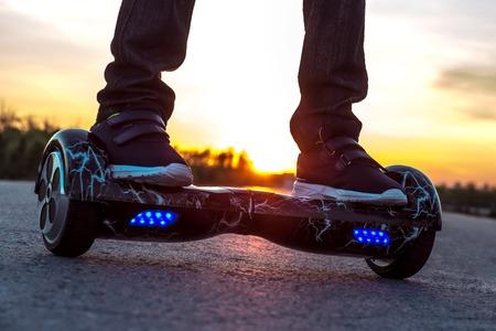 男は、日没に対する二輪車セグウェイの路上に動き始めた。