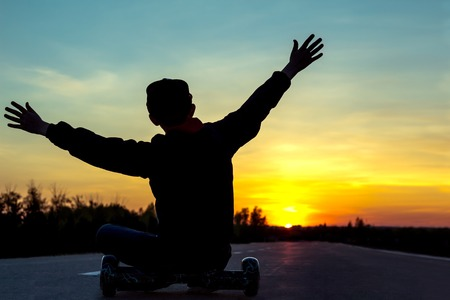 A young teenager sits on a super popular Self balancing segway scooter board, raised his hands against the sunset. Stock Photo
