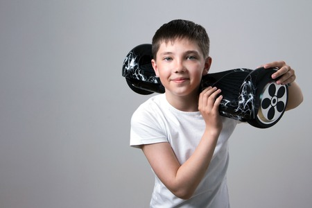 A happy teenager in a white T-shirt is holding a black self-balancing 9fcdcfdc909