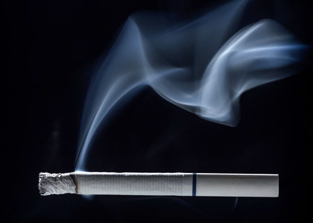 banned: Smoke and ashes on a white cigarette with a white filter and blue strip on a dark background.