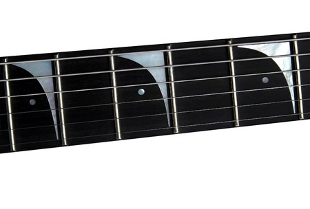 Close up top view of an electric guitar neck and strings on white background isolated.