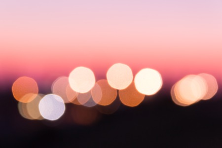 Abstract pink background in the form of blurry lights on the horizon.