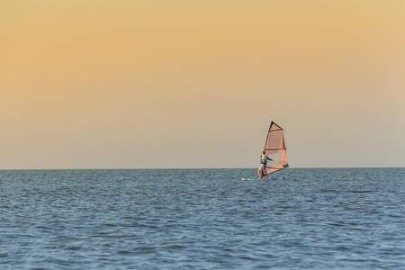 sailboard: A man is floating on the sea on a board with a sail during sunset.