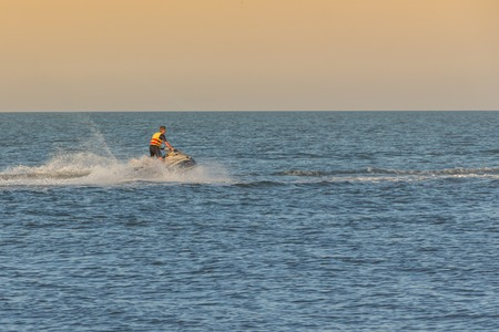 sailboard: A man in a lifejacket on a hydrocycle by the sea during sunset. Stock Photo