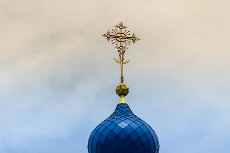 A yellow cross with a crescent on the blue dome of the temple against the sky with sunset or dawn. Stock Photo