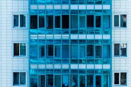 fasade: Facade of a modern urban multi-storey apartment house with blue windows.