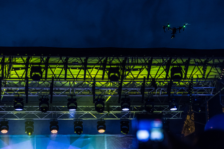 Quadrocopter with a video camera rose in the evening above the stage and shoots a video in the open air. 版權商用圖片
