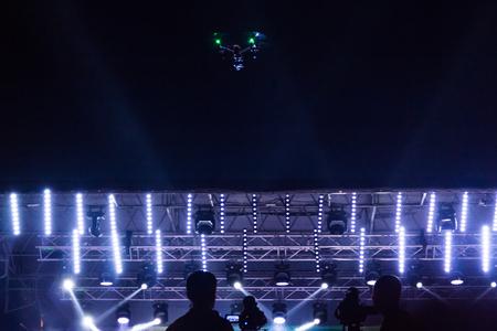 Quadrocopter in de donkere lucht over de lichten van het concertfase en videografen.