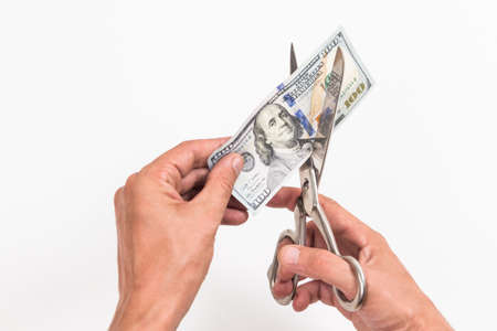 Male hands with scissors cut one hundred American dollars on a white background.