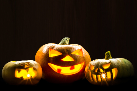 Three brightly glowing pumpkins on a dark background. Picture for decoration on the holiday of Halloween.