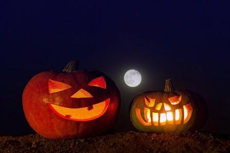 dos calabazas brillantes en el suelo y una luna llena en el cielo azul oscuro . imagen para decoración en el día de halloween