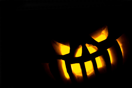 Sinisterly glowing eyes and teeth from a carved pumpkin on halloween in the lower right corner of the frame. Silhouette of the lamp of Jack on a black background. Stock Photo