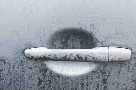 Part of the car door with a handle covered with frost.