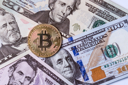 The metallic symbol of crypto currency is bitcoin against the background of dollar bills.