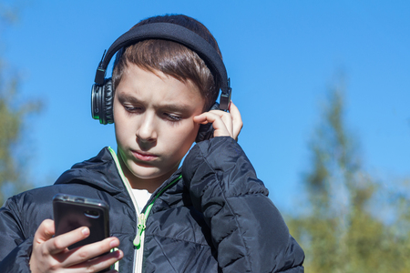A teenager in a black jacket on a sunny autumn day looks at the telephone and listens to music on headphones. Stock Photo