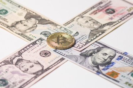 5, 20, 50 and 100 US dollars laid out with a cross with gold bitcoin in the center.