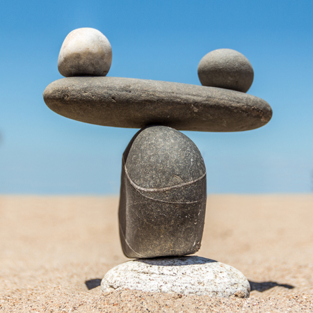 Figure in the form of weights from sea stones on a sandy beach. A square picture.