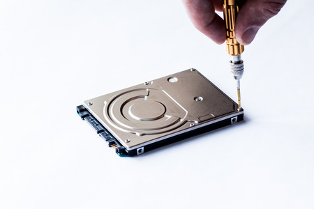 disco duro: Repair of hard disk for laptop. The computer master wipes the screw with a screwdriver.