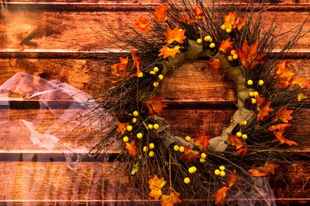 Autumn wreath of branches, leaves of yellow berries and burlap. Decorative element of the holiday halloween.