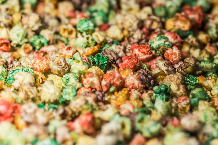 molasses: Texture background of multi colored caramel popcorn. Close-up.
