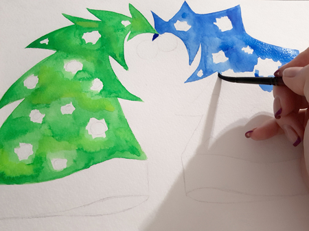 The girls hand draws a blue and green fir-tree with a watercolor paint.