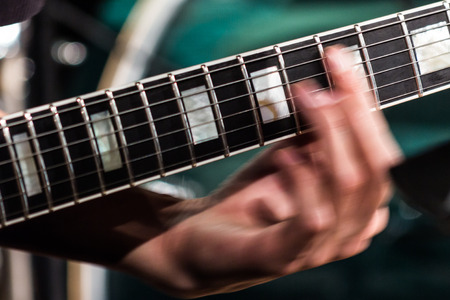 The musician's hand is blurred in motion on the fretboard on the strings of an electric guitar.