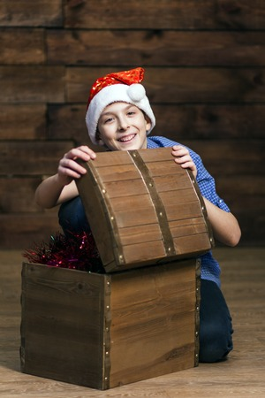 Vertical photo. A typical European teenager looks into the camera and laughs when he opens a wooden chest with Christmas ornaments.