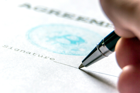 A ballpoint pen in the persons hand on a piece of paper with a bitcoin stamp puts a signature. Macro. The concept of the contract of purchase for bit-coin.