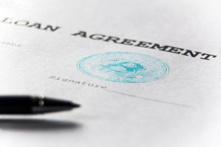 Timbre bleu de la monnaie virtuelle bitcoin sur un contrat de prêt. La place pour la signature et le stylo sont flous. Macro Faible profondeur de champ. Banque d'images - 93214259