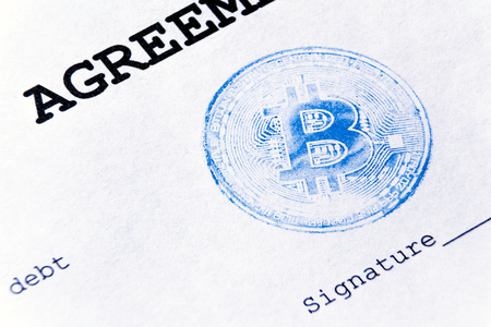 Blue stamp of virtual currency bitcoin on a loan agreement. The loan agreement, the signature is printed on a white sheet of paper. Macro. Stock Photo