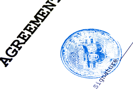 The concept of any virtual financial document with a crypto currency. Close-up. Blue stamp of virtual currency bitcoin on a loan agreement. Stock Photo