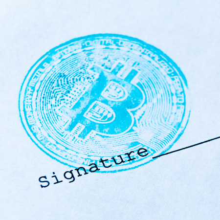 Macro. Square picture. Blue bitcoin stamp and signature on a white sheet of paper. The concept of any virtual financial document with a crypto currency. Close-up. Shallow depth of field.
