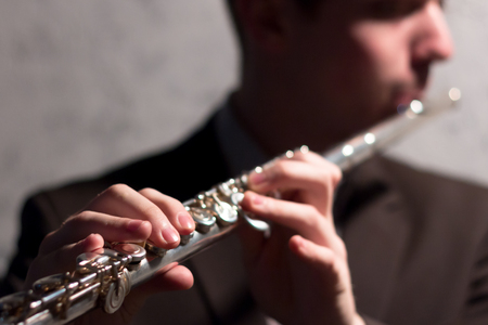 The guy is playing the flute. The hands of the man press the keys. Close-up. Shallow depth of field. Musical theme. Gray background. Imagens - 102939400
