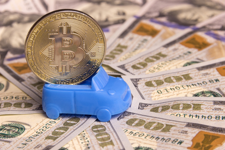 Concept of high cost, money exchange, car loan or purchase of vehicles for crypto currency. A miniature retro cabriolet carries gold bitcoin against the background of hundred-dollar bills spread out in a circle. Close-up. Stock Photo