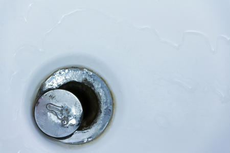 An old sewer drain in a bathtub or shower with a pattern of a human foot on the plug. Concept on repairing plumbing. Copy space for an inscription or background design.