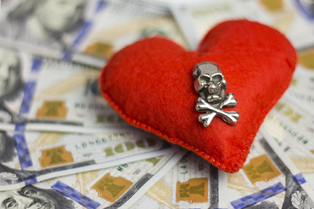 Dollars, heart, death. Concept Piracy and feelings, Wedding contract, dangerous love for money, terrible Valentines Day. Shallow depth of field. Close-up.