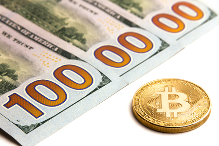 What cryptocurrency exchange rate. Gold bitcoin next to US banknotes. One million dolars. Three hundred dollar bills. White background.