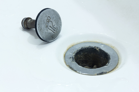 Concept on repairing plumbing. Copyspace. The old broken cork in the bathroom or shower is next to the sewer drain hole.