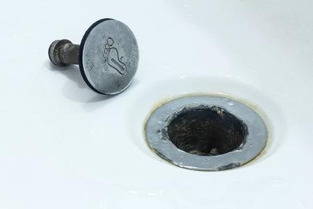 Concept bij het herstellen van loodgieterswerk. Copyspace. De oude gebroken kurk in de badkamer of douche bevindt zich naast het rioolafvoergat.