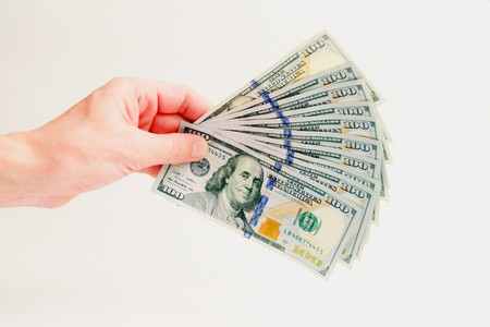 How to earn and cash money. A fan of hundred-dollar bills. A thousand dollars in the left male hand on a white background. Isolated. Close-up. Stock Photo