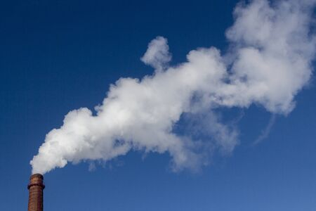 Thick white smoke comes from the brick industrial factory pipe into the sky. Atmosphere, industry and ecology concept.