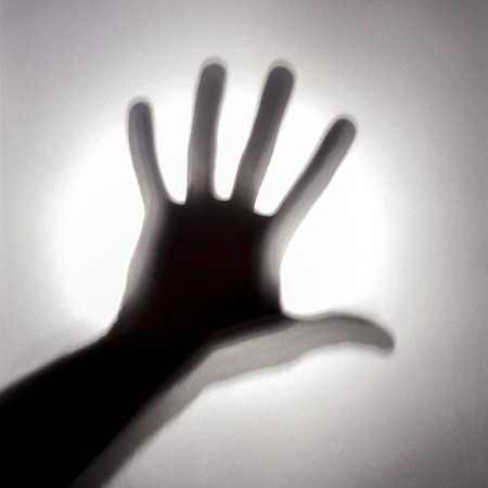 Abstract silhouette of a mans hand on the background of a bright light spot. A mystical square picture on a noisy background behind a frosted glass. Concept call for help or a terrible story. Banco de Imagens - 98134520