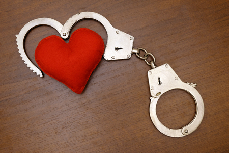Red soft heart and real steel police handcuffs on a brown background. The concept of love and the law. Stock Photo
