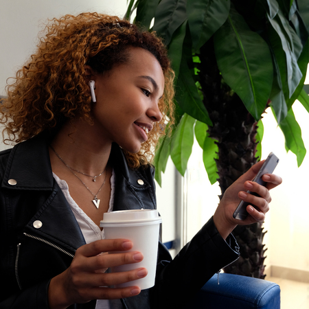 A square picture. A beautiful young African-American girl in a black jacket with airpairs in her ear smiles, holds a white glass in her hand and looks at the phone next to the palm tree. Stockfoto