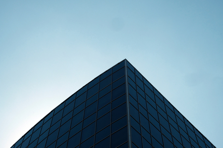 The angle of the modern building from the dark blue glass is directed to the sky. Copy space. Atmosphere of urban office life.