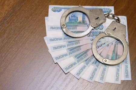 The concept of violation of the law in the financial sphere, corruption, bribery, fraud. Ten Russian bills of one thousand rubles with handcuffs lie on a brown table.